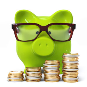 Green piggy bank with glasses and coin stacks