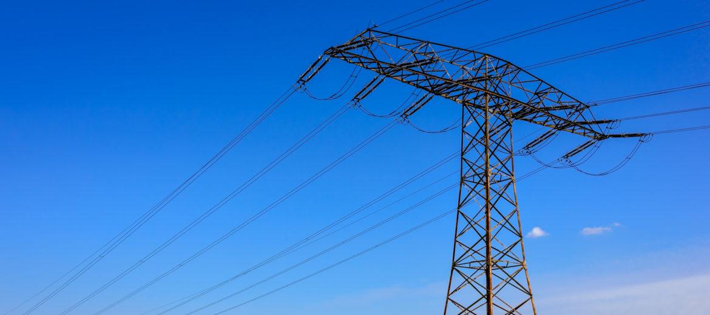 Strommast in einem blhenden Rapsfeld in Brandenburg