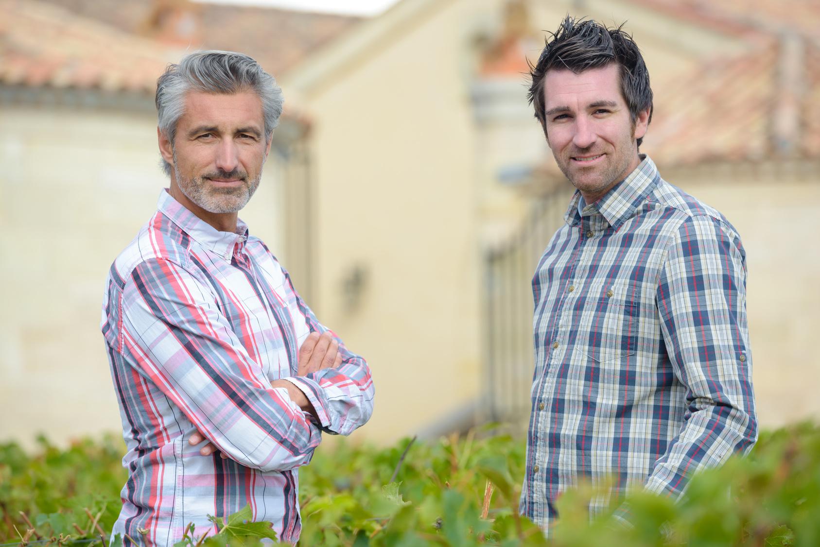 Zwei Nachbarn stehen an geschnittener Hecke